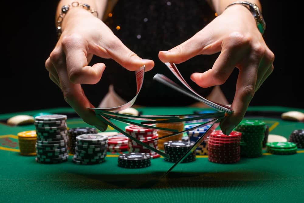 Girl dealer or croupier shuffles poker cards in a casino