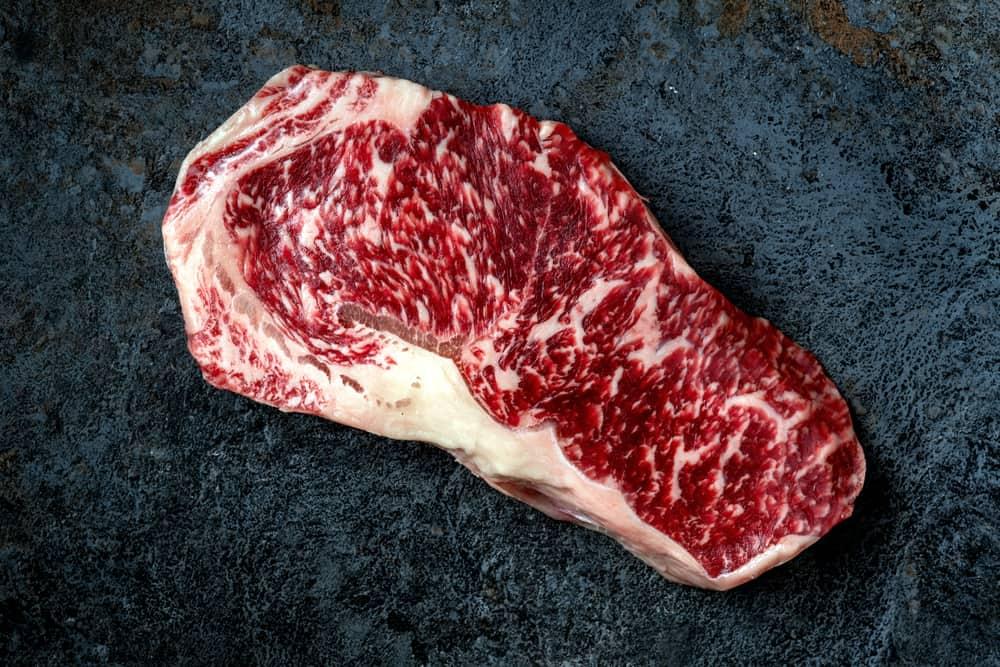 Raw Wagyu beef striploin steak on stone table