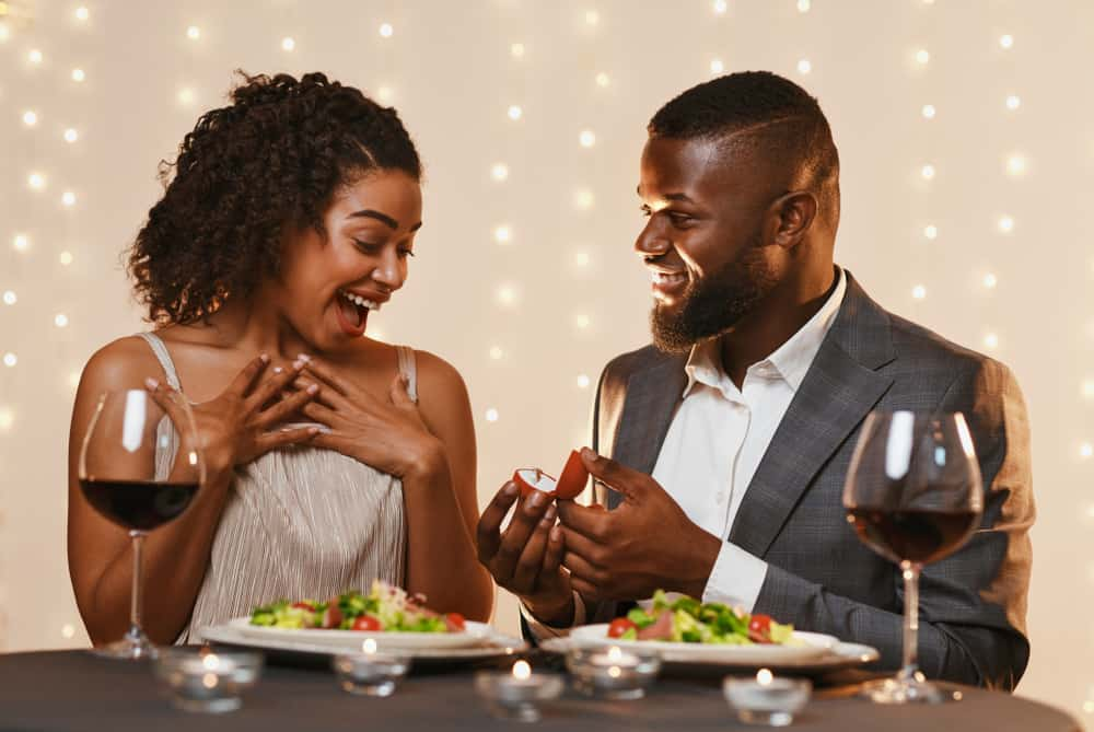 man making marriage proposal to his surprised beautiful woman