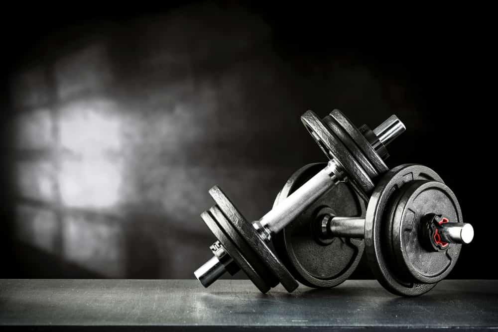 Dark gym interior with black dumbbells