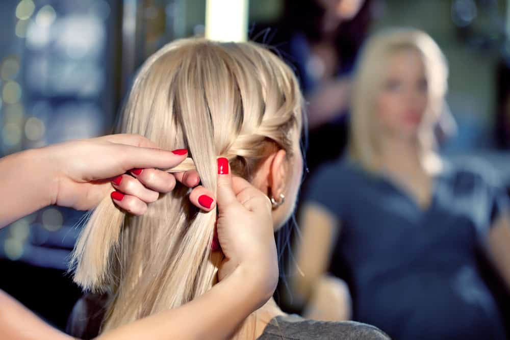 Hairdresser make French braids in beauty salon