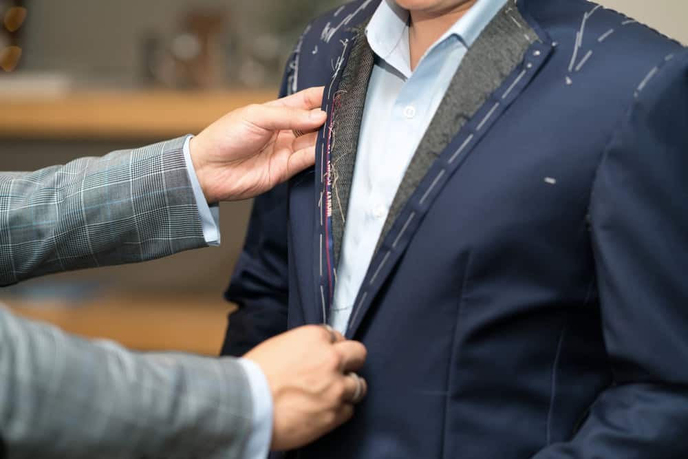 Tailor measures a man