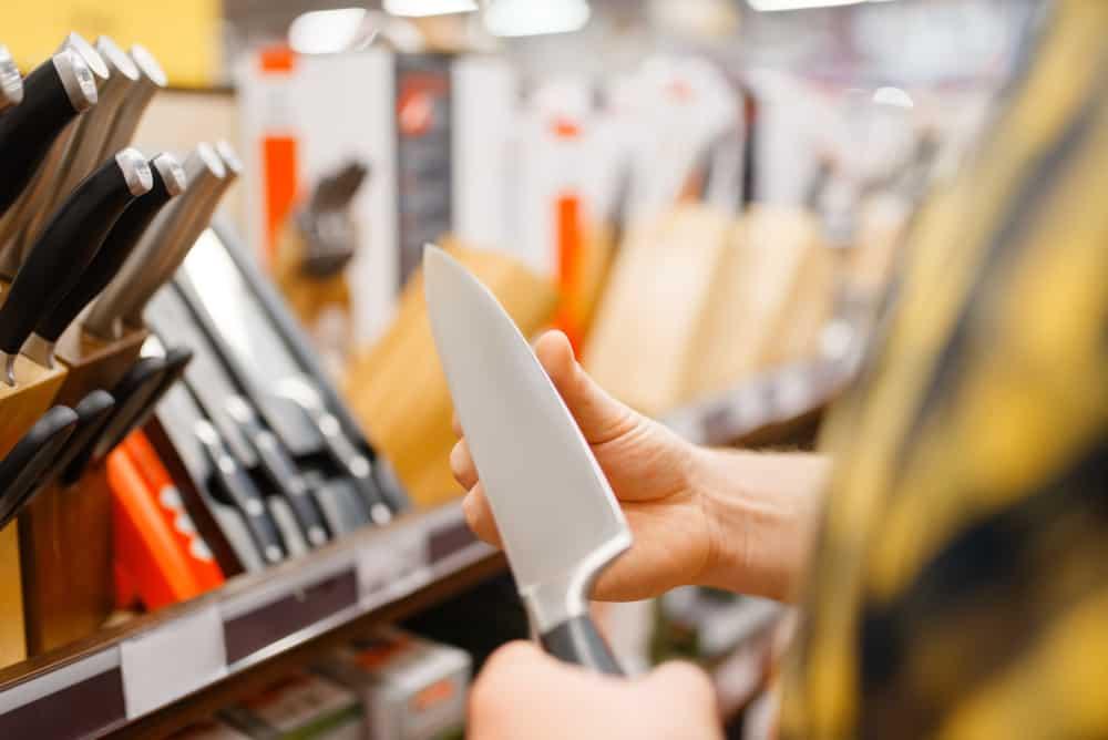 Young man choosing kitchen knife