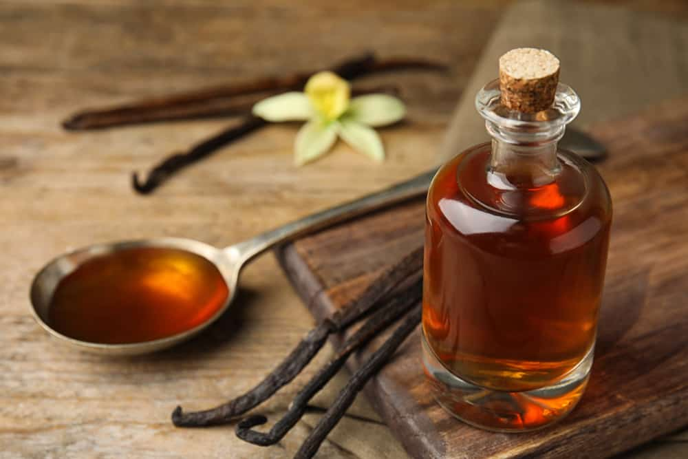 Aromatic homemade vanilla extract on wooden table, closeup